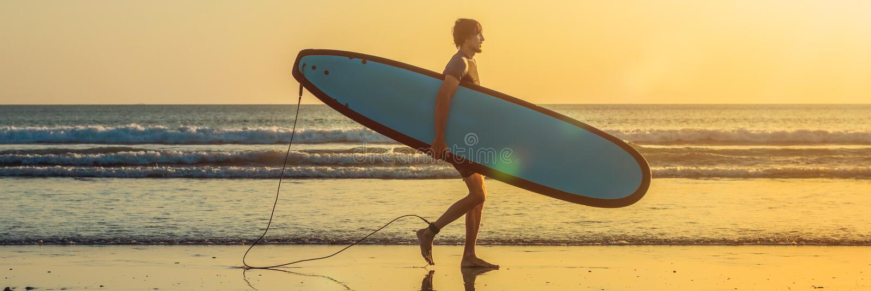 Ferien-Schattenbild eines Surfers, der sein Brandungs-Brett-Haus bei Sonnenuntergang mit Kopien-Raum FAHNE, langes Format trägt lizenzfreies stockbild