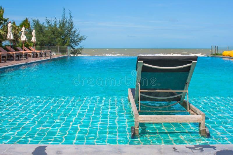 Ferien und Entspannungs-Konzept: Daybed neben Swimmingpool im Erholungsort lizenzfreies stockfoto