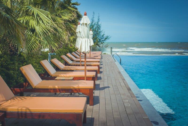 Ferien und Entspannungs-Konzept: Daybed neben Swimmingpool im Erholungsort stockfotografie