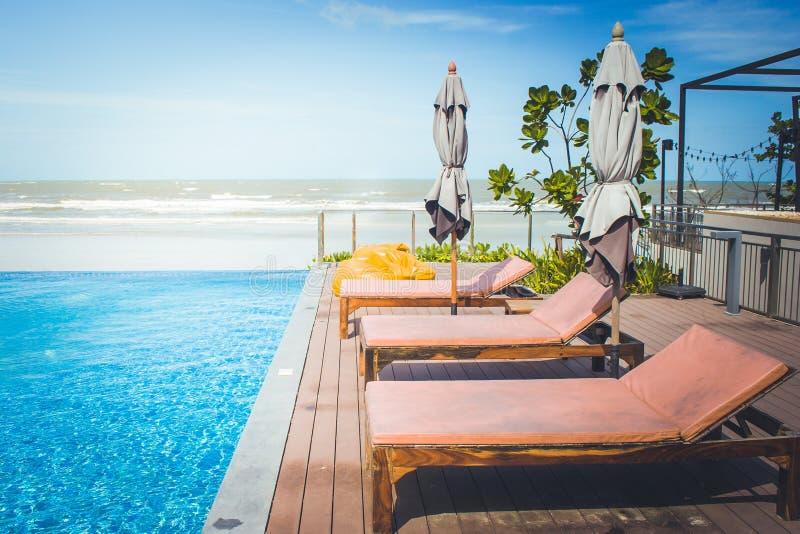 Ferien und Entspannungs-Konzept: Daybed neben Swimmingpool im Erholungsort mit See- und des blauen Himmelshintergrund stockbilder