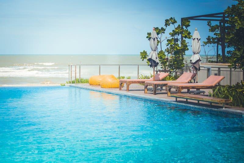 Ferien und Entspannungs-Konzept: Daybed neben Swimmingpool im Erholungsort mit See- und des blauen Himmelshintergrund lizenzfreie stockfotografie