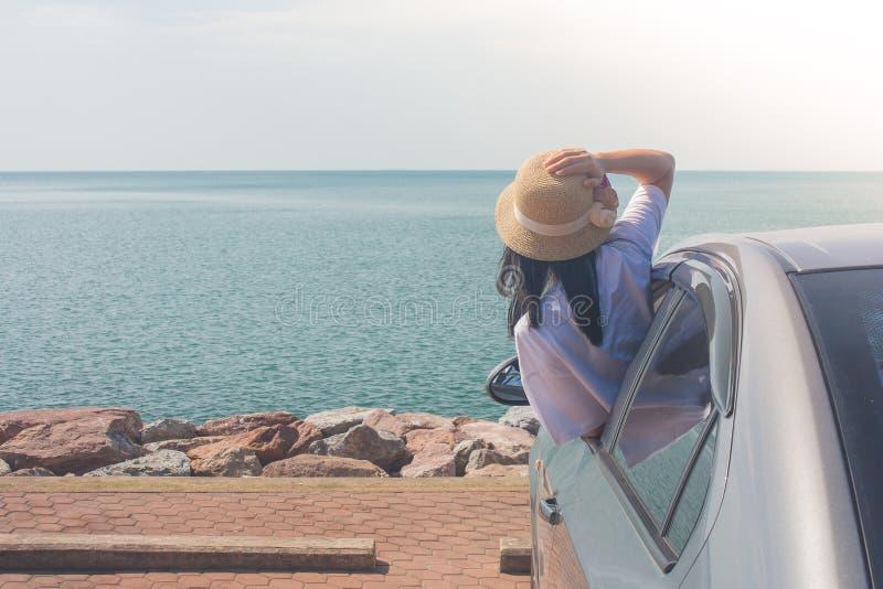 Ferien-und Feiertags-Konzept: Glückliche Familienautoreise am See-, der Porträtfrautragenden Webarthut und an glaubendem Glück stockfotos