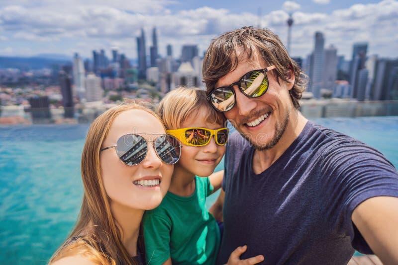Ferien und Technologie Gl?ckliche Familie mit dem Kind, das zusammen selfie nahe Swimmingpool mit Panoramablicken von nimmt lizenzfreies stockbild