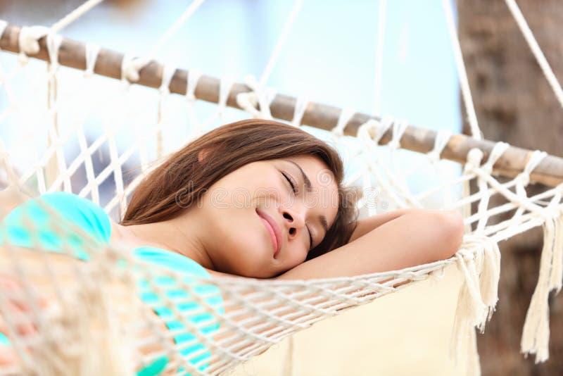 Ferienfrau beim Hängemattenschlafen stockfotografie