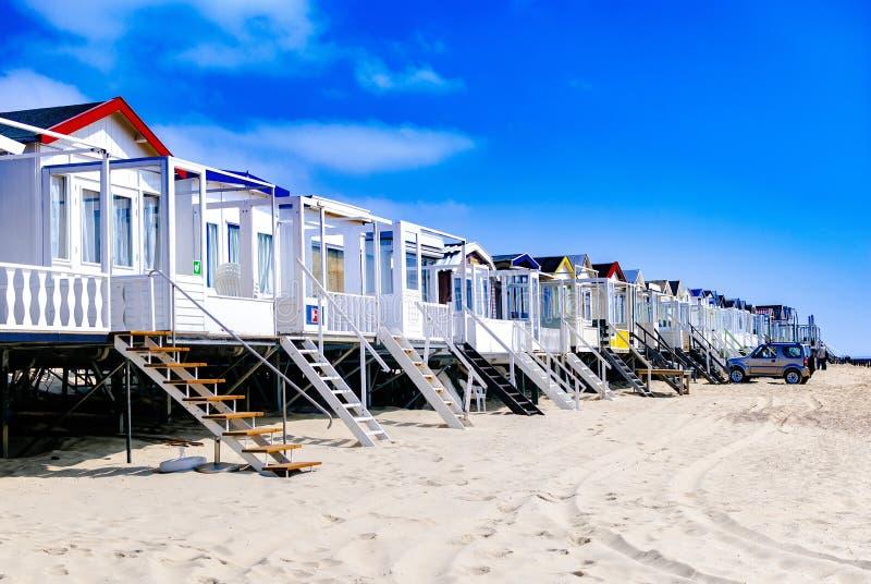 Ferienheime, die entlang der Küstenlinie stehen Seashells gestalten auf Sandhintergrund Ferienmieten rückzug stockbild