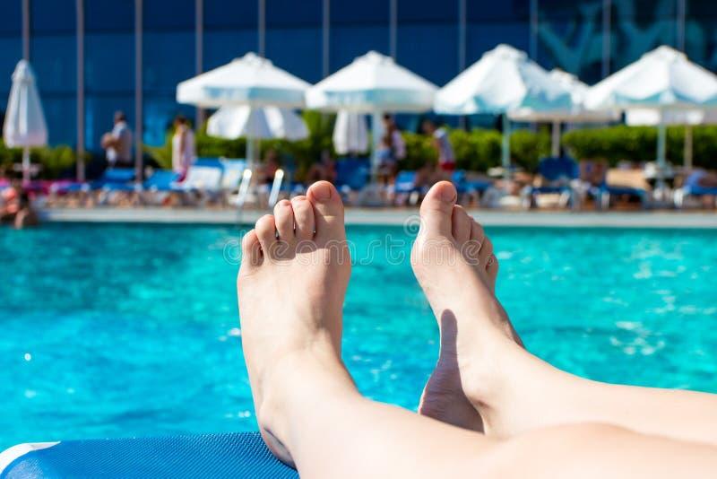 Ferienkonzept - weibliche Beine nähern sich Swimmingpool stockfoto