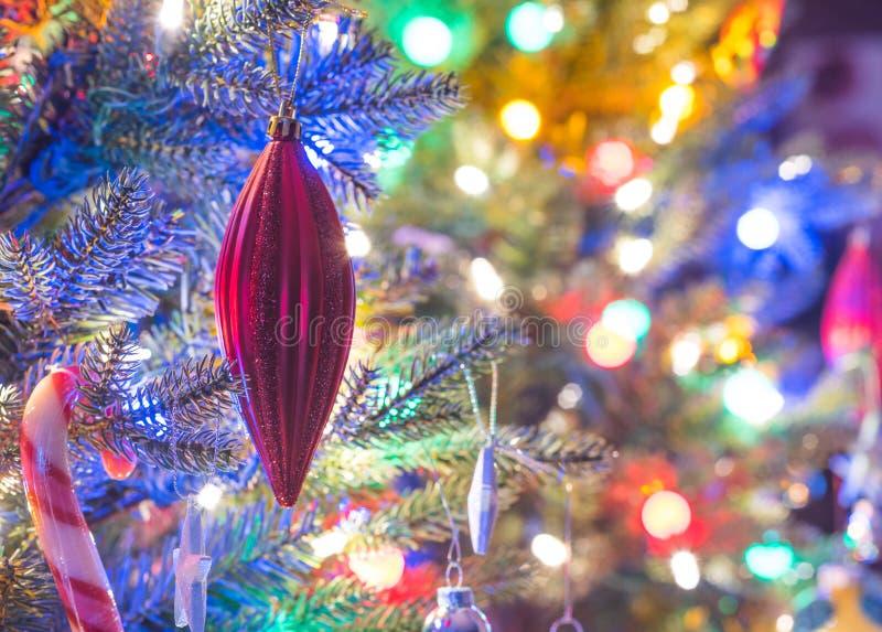 Ferienzeit, Weihnachtsbaumdekorationen glühen unter die leuchtenden und klaren, bunten Lichter auf einem Innenbaum des kleinen Fa stockbild
