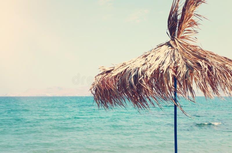 Ferier avbildar av det tropiska havet och slags solskydd som göras från torra palmblad Sommarlopp och semesterbegrepp arkivbild