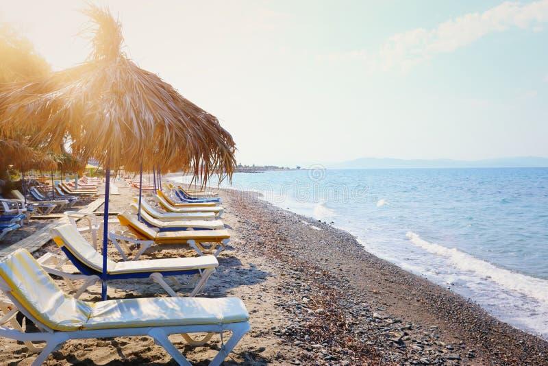 Ferier avbildar av tropiska havs- och strandstolar under paraplyer Sommarlopp och semesterbegrepp arkivfoton