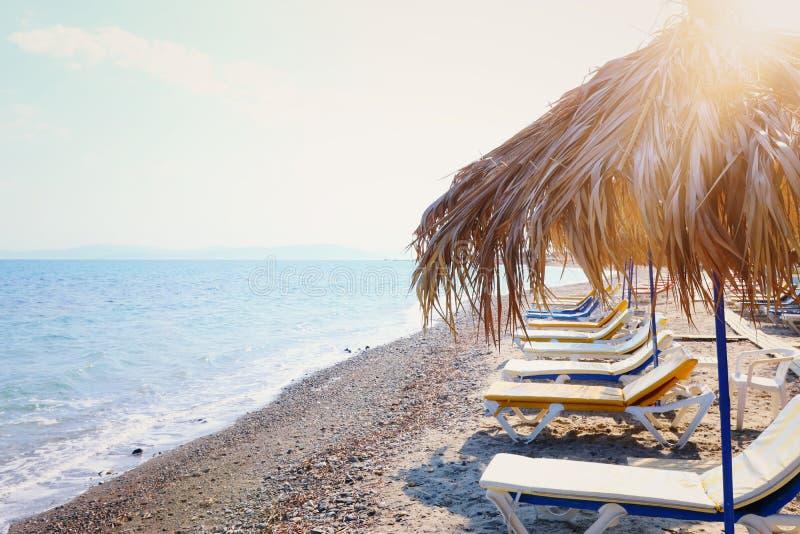 Ferier avbildar av tropiska havs- och strandstolar under paraplyer Sommarlopp och semesterbegrepp arkivbilder