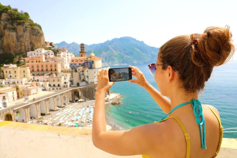 Ferier i Italien! Den härliga unga kvinnan tar bilden med den smarta telefonen av den Atrani byn på den Amalfi kusten, Italien fotografering för bildbyråer