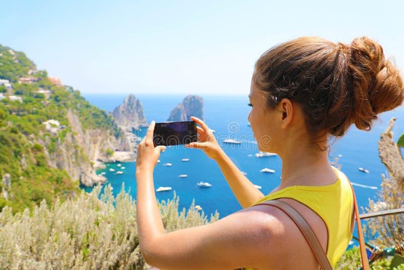 Ferier i Italien! Den härliga unga kvinnan tar bilden med den smarta telefonen av den Capri ön, Italien royaltyfria foton