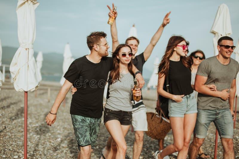 ferier semester grupp av vänner som har gyckel på stranden, att gå, drinköl, att le och att krama arkivfoton