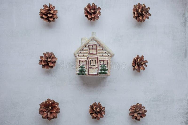 ferier, vinter och berömbegrepp - julsammansättning sörja kottar, leksakhus i mitten på cement royaltyfri foto
