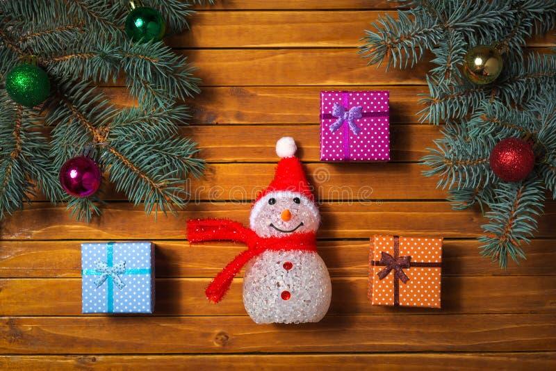 Feriesammansättning med gran förgrena sig, gåvaboxies, leksakbollar och leksaksnögubben fotografering för bildbyråer