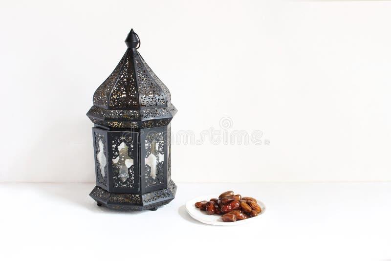 Feriestillebensammansättning Platta med datumfrukter och den dekorativa mörka marockanska arabiska lyktan på den vita tabellen arkivfoto