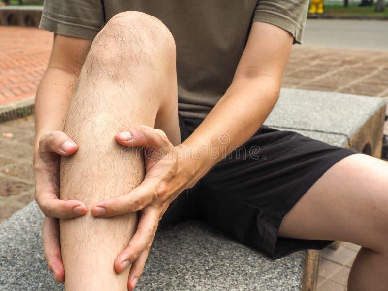 Ferimento running do esporte corredor vestindo do homem do basculador masculino do atleta que faz massagens o músculo da vitela a foto de stock