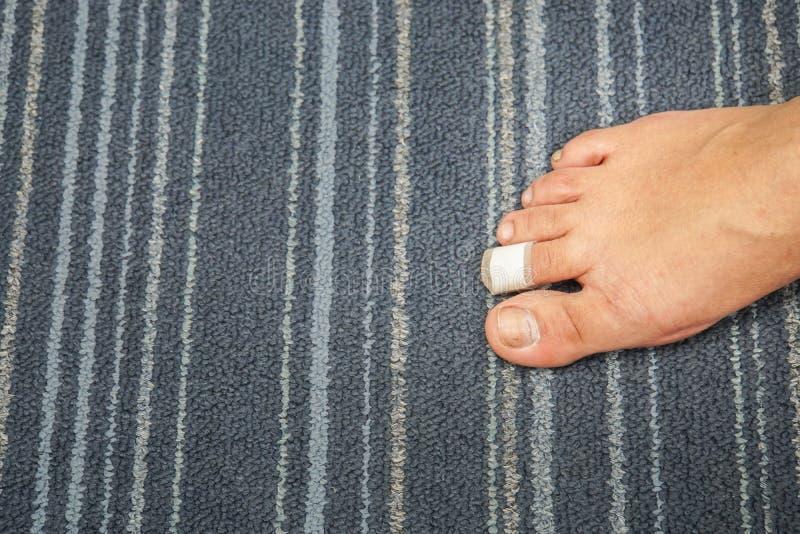 Ferisca al piede destro del dito del piede della donna curativo con l'aiuto di banda fotografie stock