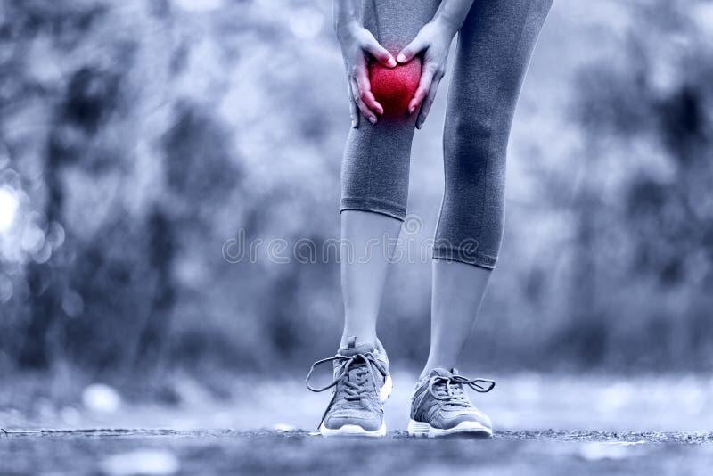 Ferita al ginocchio - sport che eseguono le ferite al ginocchio sulla donna fotografia stock