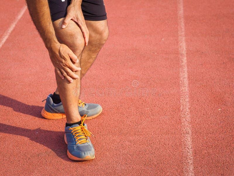 Ferite al ginocchio metta in mostra l'uomo con le forti gambe atletiche che tengono il ginocchio fotografia stock libera da diritti