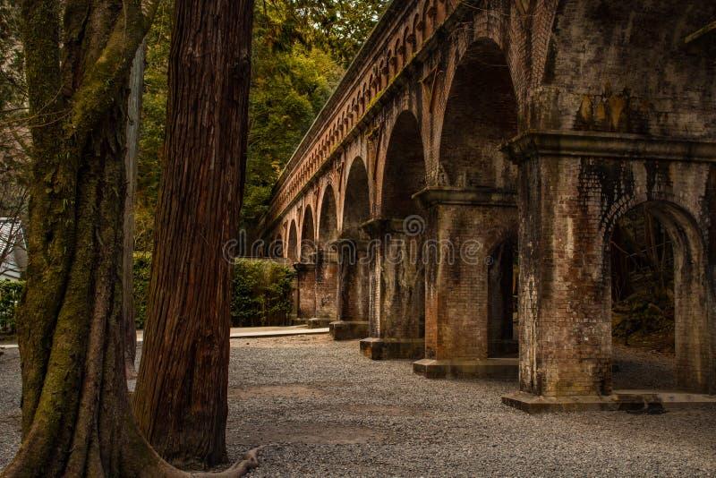 Fermé d'un pont de brique rouge dans le temple de Nanzen-JI entouré par les arbres et la forêt images libres de droits