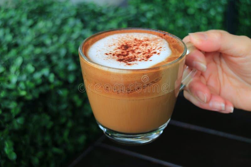 Fermé vers le haut d'une tasse de café chaud de cappuccino se tenant chez la main du ` s de la femme, avec Bush vert brouillé à l photo libre de droits