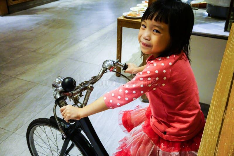 Fermé vers le haut de la fille de sourire asiatique portant les vêtements roses sur le BIC de vintage photo libre de droits