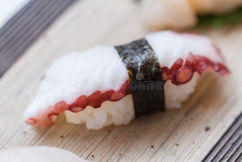 Fermé vers le haut des sushi de tentacule de calmar des sushi réglés du plat en pierre photos stock