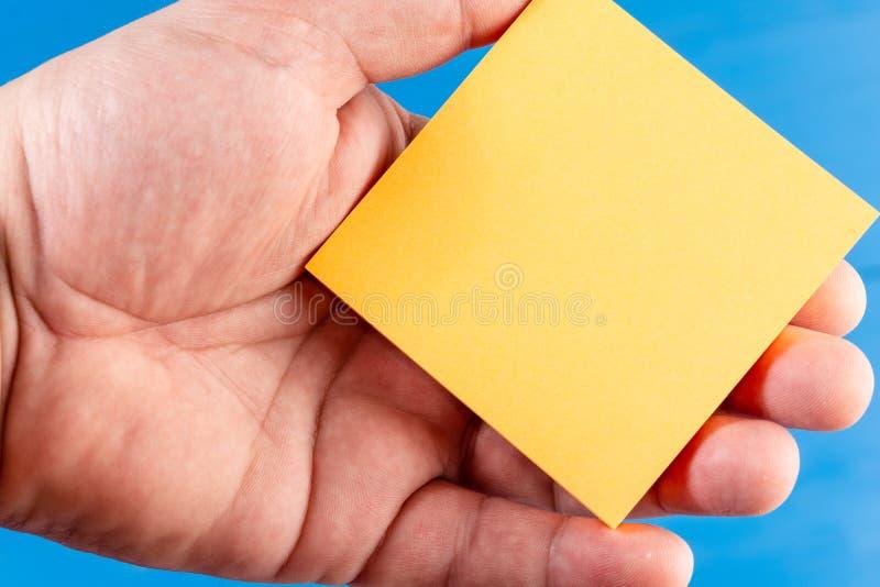 Ferm? vers le haut de la main d'homme de fond color?e par vue tenant la note collante La feuille de papier carr? a tenu la paume  photo libre de droits