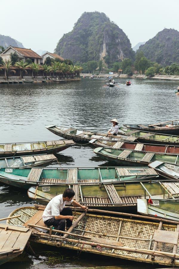 Fermata della barca sul fiume con molte barche di fila vuote, remando gli uomini e le donne con la montagna nei precedenti di est fotografia stock libera da diritti