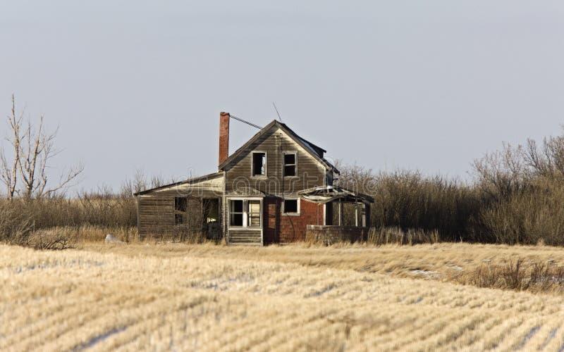 Ferme abandonnée par prairie photo stock