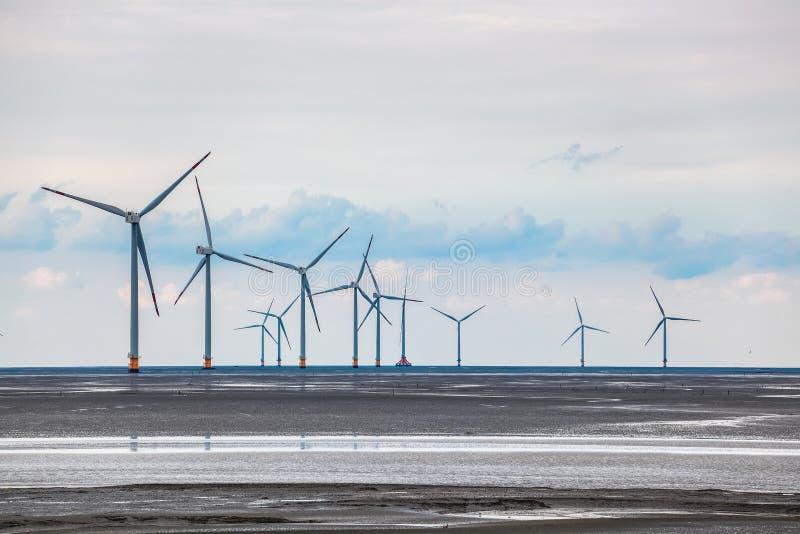 Ferme d'énergie éolienne dans l'appartement de boue côtier images libres de droits