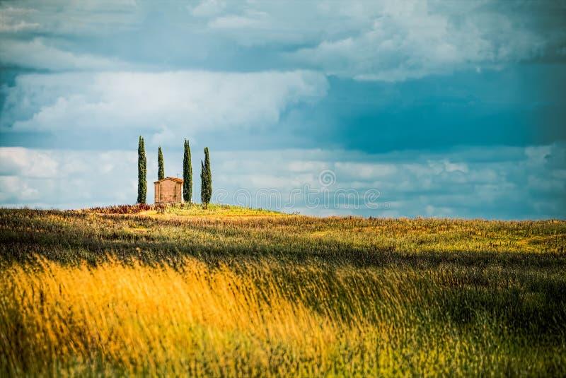 Ferme d'isolement parmi quatre cyprès sur une colline en Toscane tandis qu'une tempête vient photo stock