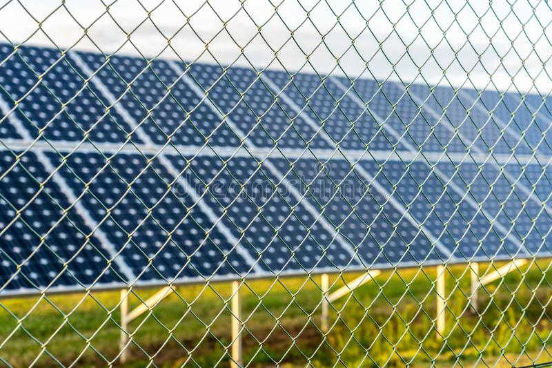 Ferme solaire avec les panneaux photovoltaïques derrière la barrière photo libre de droits