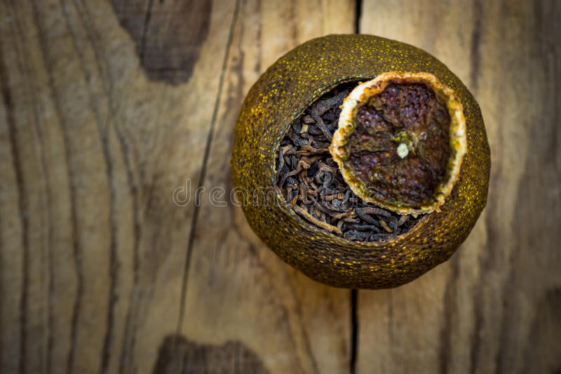 Fermented变老了在蜜桔干燥果皮的黑中国puer茶与盒盖,被风化的木背景,顶视图 库存图片