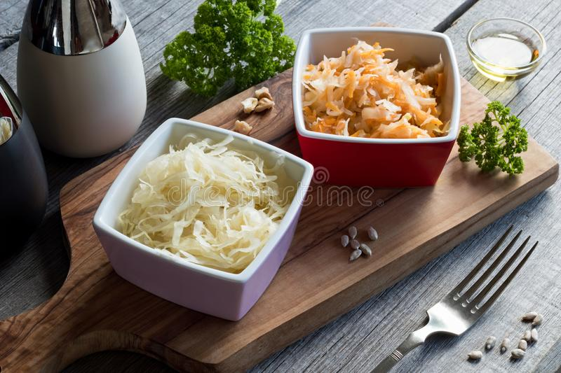 Fermented cabbage and carrots in two square bowls on a table stock image