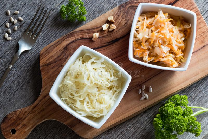 Fermented cabbage and carrots in two square bowls on a table, to stock images