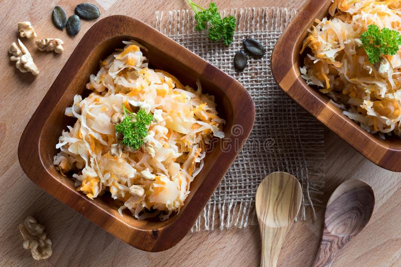 Fermented cabbage and carrots in two wooden bowls stock images