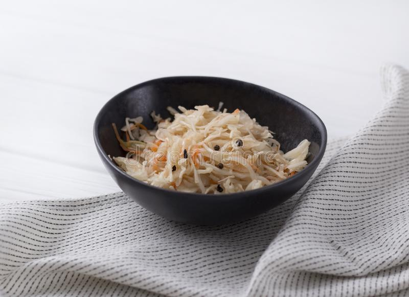 Fermented cabbage. Traditional russian appetizer sauerkraut with carrot in craft plate on white wooden table stock images