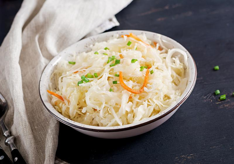 Fermented cabbage. Vegan food. Sauerkraut with carrot and spices in bowl royalty free stock images