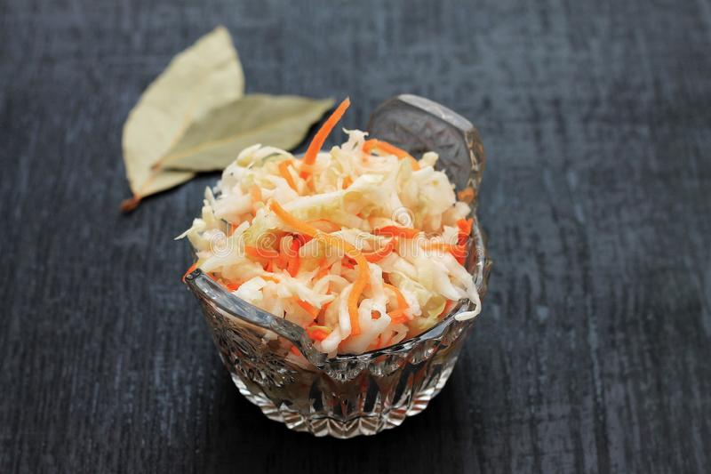Fermented cabbage. Vegan food. Sauerkraut with carrot and spices in bowl on the dark background. Trend food royalty free stock photography