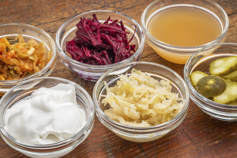 Fermented food collection. A sampler of fermented food great for gut health - glass bowls against wood: kimchi, red beets, apple cider vinegar, coconut milk stock image