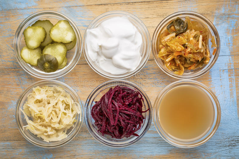 Fermented food collection. A set of fermented food great for gut health - top view of glass bowls against grunge wood: cucumber pickles, coconut milk yogurt royalty free stock photography