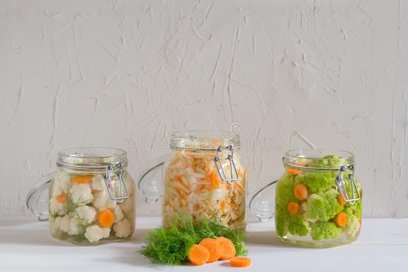 Fermented a préservé le concept végétarien de nourriture Chou, brocoli, caulie, pots en verre aigres de choucroute sur le fond bl image stock