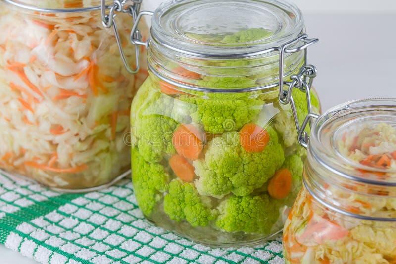 Fermented a préservé le concept végétarien de nourriture Chou, brocoli, caulie, pots en verre aigres de choucroute sur le fond bl photographie stock