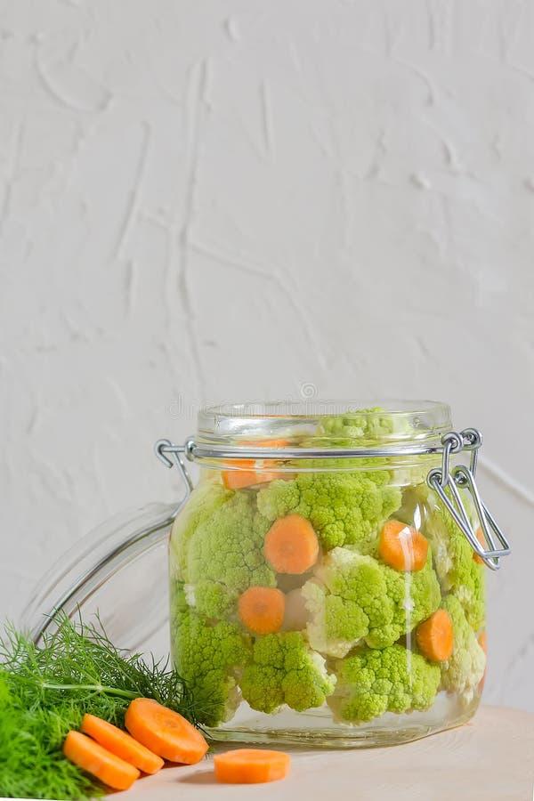 Fermented a préservé le concept végétarien de nourriture pots en verre aigres verts de chou-fleur ou de brocoli sur le fond blanc photo stock