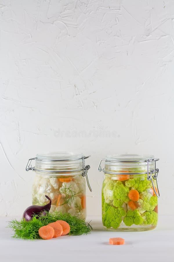 Fermented a préservé le concept végétarien de nourriture pots en verre aigres verts de chou-fleur ou de brocoli sur le fond blanc photographie stock