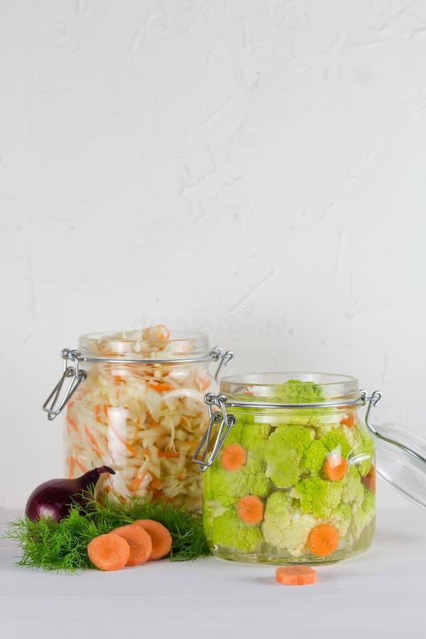 Fermented a préservé le concept végétarien de nourriture pots en verre aigres verts de chou-fleur ou de brocoli sur le fond blanc image stock