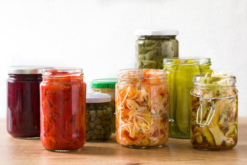 Fermented preserved vegetables in jar on wood. En table stock images