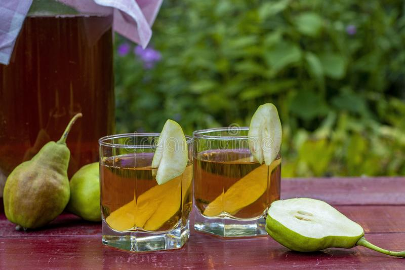Fermented Raw Kombucha Tea with Pears, Summer Healthy Detox Drink in jar and two glass, Horizontal Orientation. Homemade Fermented Raw Kombucha Tea with Pears royalty free stock photos